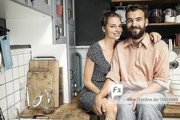 Junges Paar sitzt auf der Küchenarbeitsplatte und lächelt