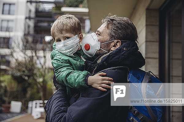 Father carrying son  both wearing protective maska  outdoors