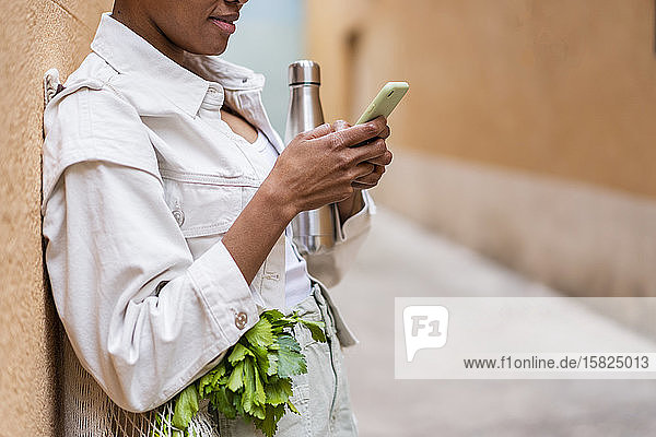 An die Wand gelehnte Frau mit Thermoskanne und Lebensmitteln per Smartphone