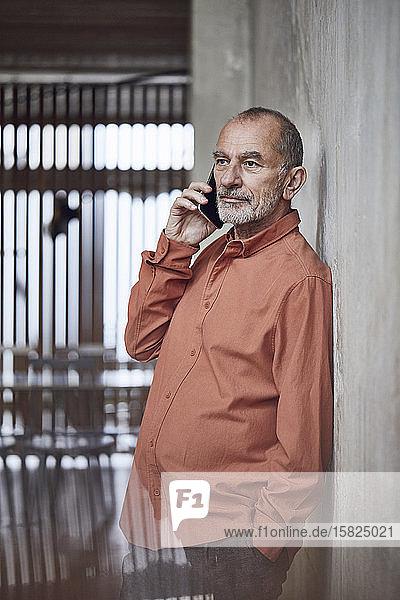 Kreativer Geschäftsmann telefoniert in seinem minimalistischen Büro