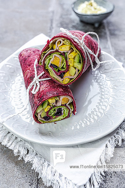 Beetroot wraps filled withham  cheese  corn  iceberg lettuce  cucumbers and cream cheese