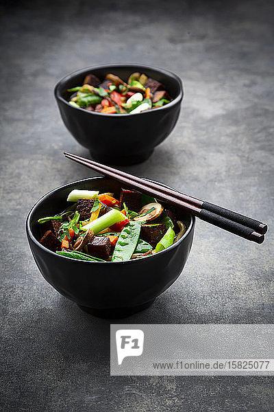 Zwei Schüsseln verzehrfertige Misosuppe mit Udon-Nudeln  Tofu  Zuckererbsen  Paprika  Karotten  Mu-err-Pilzen  Schalotten und Koriander