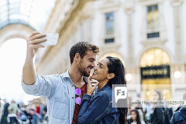Glückliches junges Paar  das ein Selfie in der Stadt macht  Mailand  Italien Glückliches junges Paar, das ein Selfie in der Stadt macht, Mailand, Italien