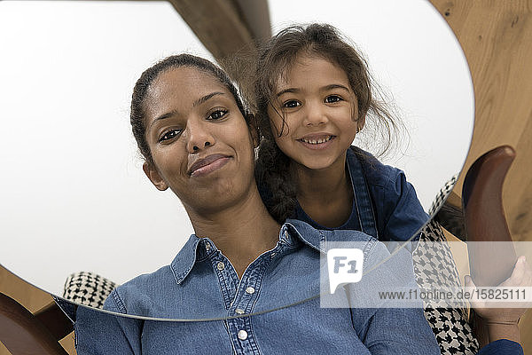 Mirror image of smiling mother and her happy little daughter