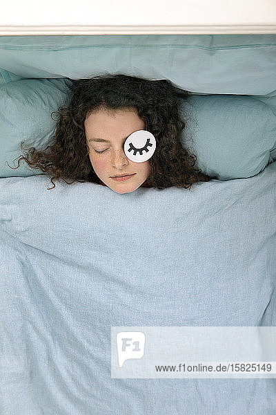 Portrait of sleeping young woman lying in bed with paper mask