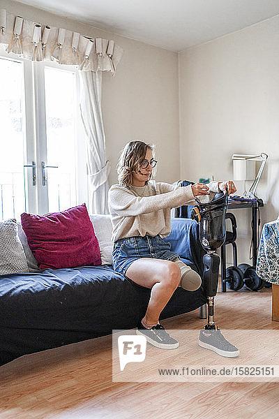Junge Frau mit Beinprothese sitzt zu Hause auf einer Couch