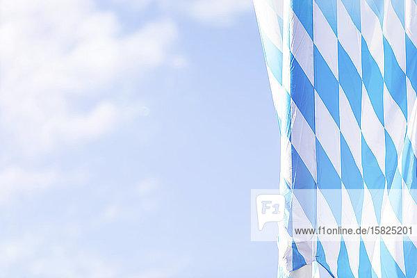 Deutschland  Bayern  München  Niederwinkelansicht der bayerischen Flagge  die während des Oktoberfestes am Himmel hängt