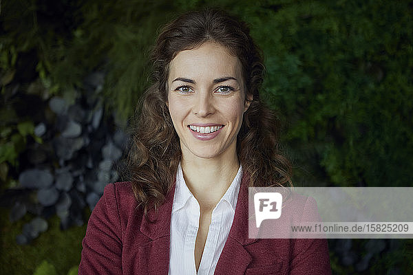 Portait of smiling businesswoman in green office