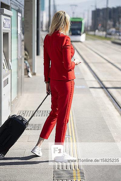 Blonde Geschäftsfrau im roten Anzug  die auf den nächsten Zug wartet