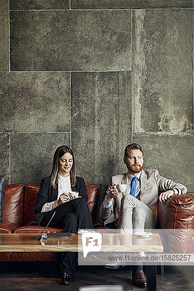 Businessman and businesswoman sitting on couch in hotel lobby having a coffee break
