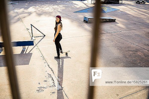 Young woman with skateboard at skatepark