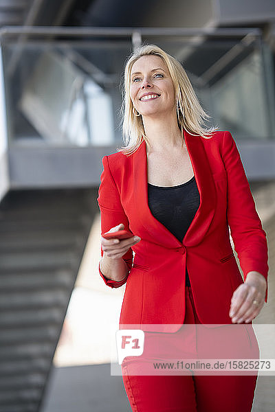 Blond smiling businesswoman wearing red suit and holding smartphone