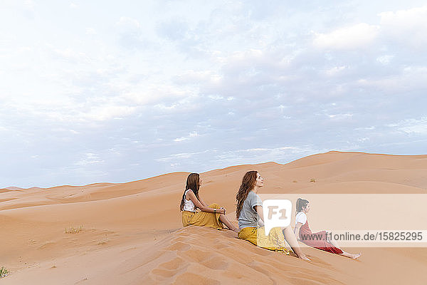 Drei junge Frauen sitzen in einer Sanddüne in der Wüste Sahara  Merzouga  Marokko