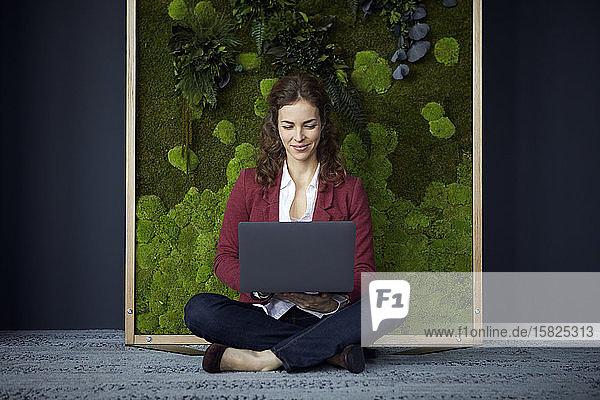 Lächelnde Geschäftsfrau sitzt in grünem Büro mit Laptop auf dem Boden