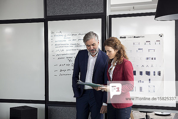 Businessman and businesswoman working together on a project in office