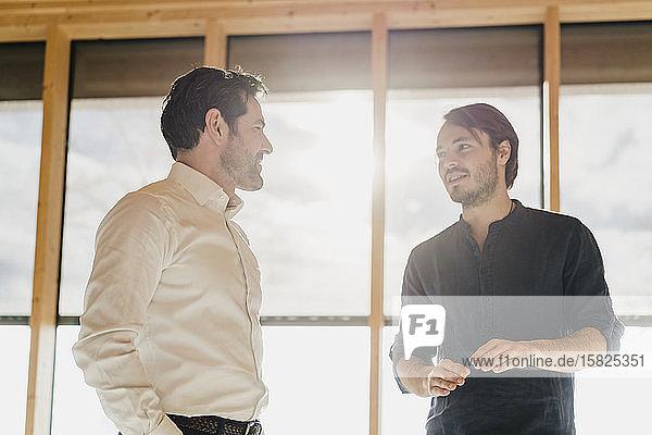 Zwei Geschäftsleute im Gespräch am Fenster im Büro