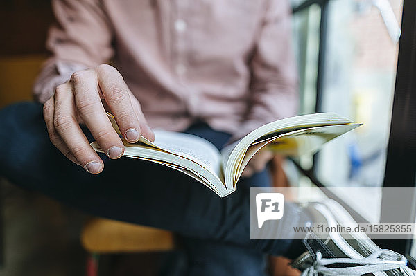 Nahaufnahme eines Mannes  der ein Buch am Fenster liest