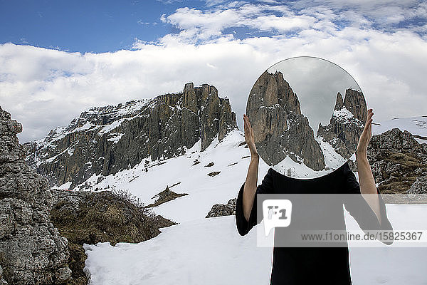 Woman covering head with mirror  reflecting Sella group in winter  Dolomites  Alto Adige  Italy