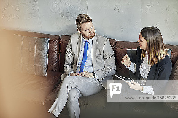 Businessman and businesswoman with tablet sitting on couch in hotel lobby