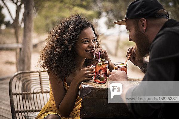Glückliches Paar trinkt gemeinsam frischen Eistee