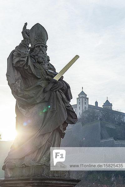 Deutschland  Bayern  Würzburg  Würzburg  Statue des Heiligen Kilian bei Sonnenuntergang mit der Festung Marienberg im Hintergrund