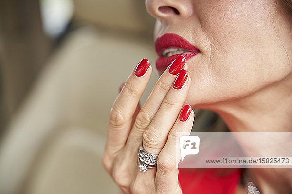 Schnittansicht einer reifen Frau mit roten Lippen und Nägeln
