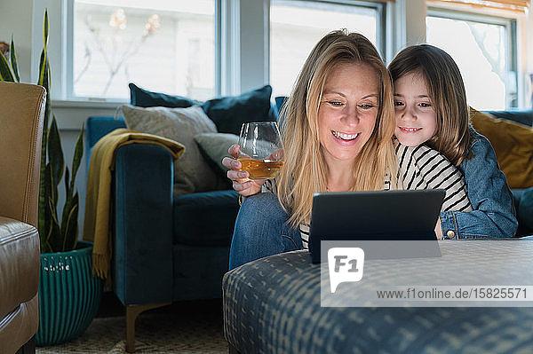 Mutter und Tochter (6-7) schauen zu Hause auf den Laptop