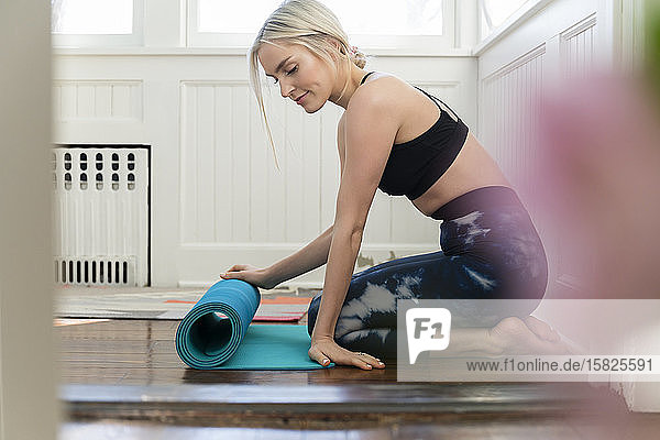Young woman unrolling yoga mat at home