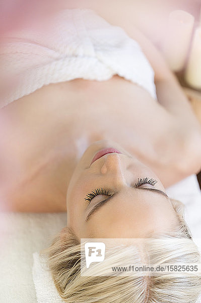 Woman relaxing lying on back on massage table