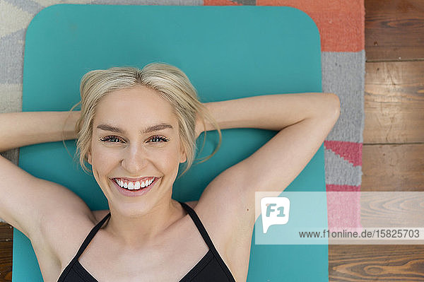 Blonde smiling woman lying on back on yoga mat