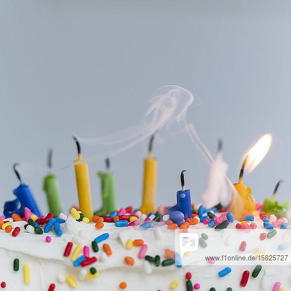 Ausgelöschte Geburtstagskerzen auf dem Kuchen - eine brennt noch