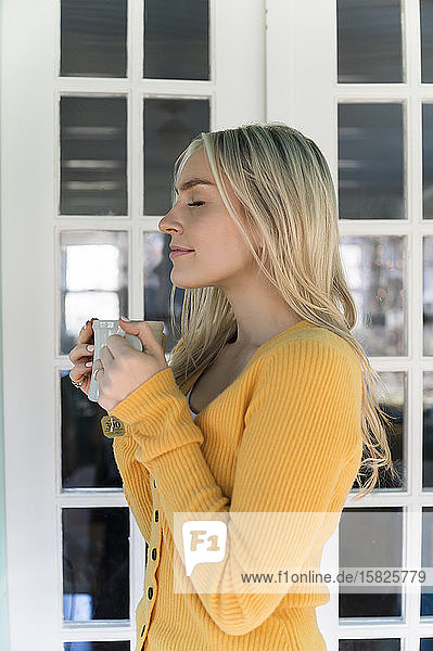 Portrait of woman in yellow sweater holding mug