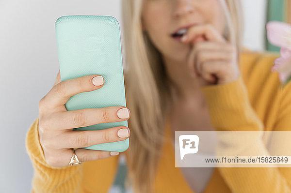 Frau hält Smartphone und kaut auf den Nägeln