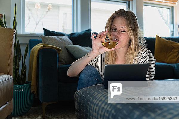 Frau trinkt Wein und schaut auf ein Tablet zu Hause