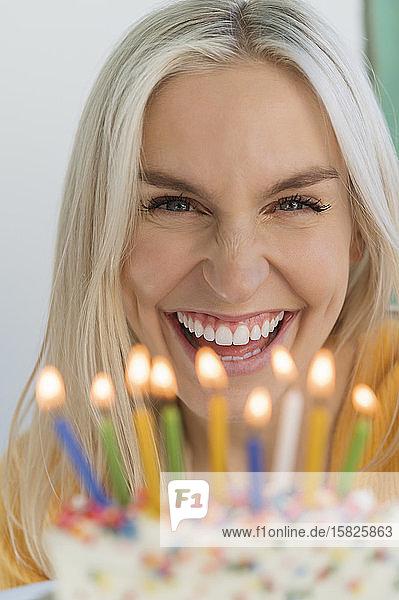 Frau lächelnd hinter Geburtstagskerzen