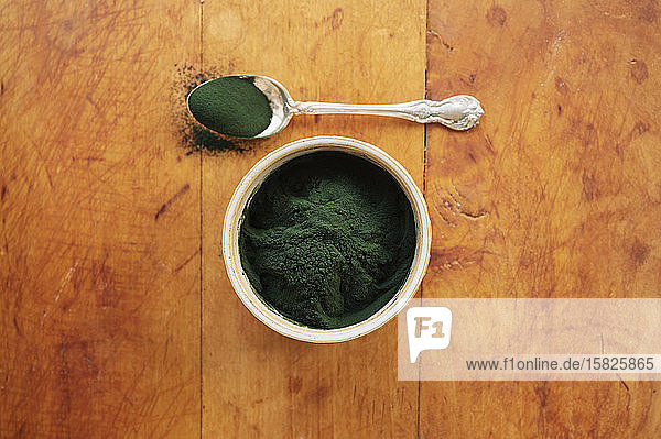 Spirulina in bowl and spoon full against wood