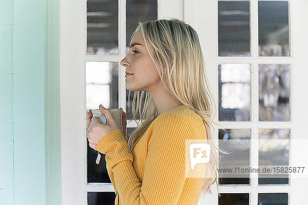 Porträt einer Frau im gelben Pullover mit Tasse