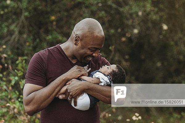Nahaufnahme des glücklichen Vaters  der das neugeborene Mädchen draußen hält und anlächelt