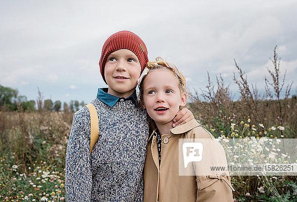 Bruder und Schwester stehen sich im Herbst umarmend in einem Feld mit Wildblumen