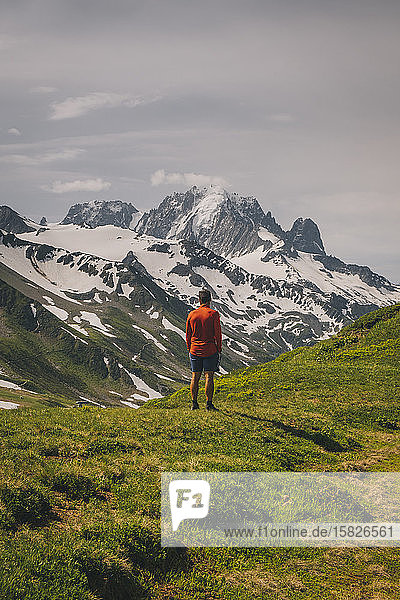 Young male stands looking at the Mont Blanc massif  Chamonix  France.