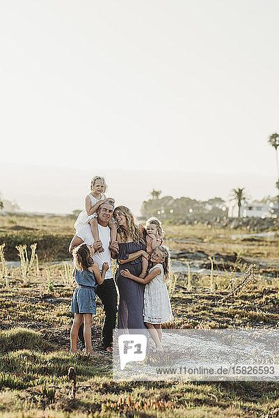 Lifestyle-Porträt einer Familie mit jungen Mädchen  die bei Sonnenuntergang am Strand lächeln