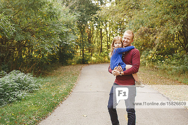 A smiling father holds small daughter in his arms on a tree-lined path