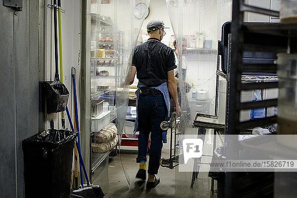 Rückansicht eines Arbeiters auf dem Vorfeld beim Betreten einer hell erleuchteten Küche