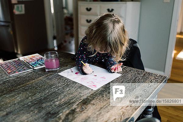 Little girl having a ball painting with her mother.