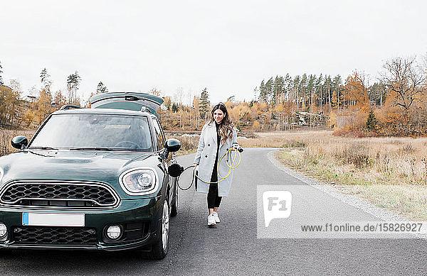 Frau  die zu Fuß geht  um ihr Elektroauto an eine Steckdose auf dem Land anzuschließen