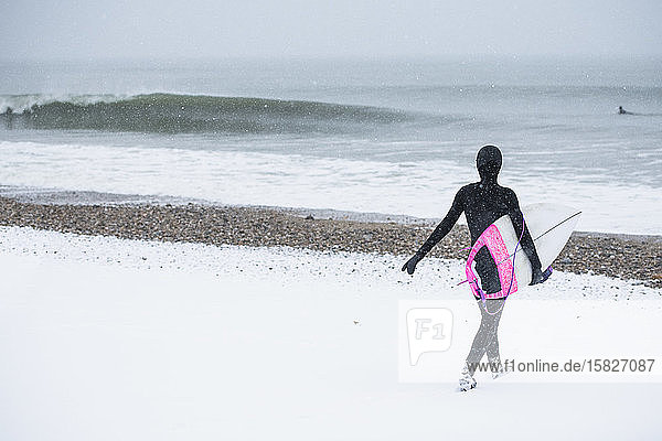 Woman going surfing during winter snow