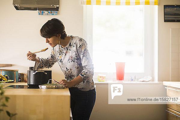 eine junge Frau  die zu Hause in einer Küche kocht