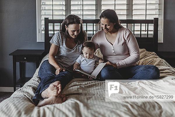 Gleichgeschlechtliche Eltern lesen im Bett mit einer 8 Monate alten Tochter