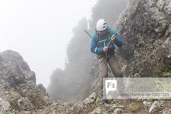 Bergsteiger bereitet sich auf das Abseilen einer Kletterroute vor.
