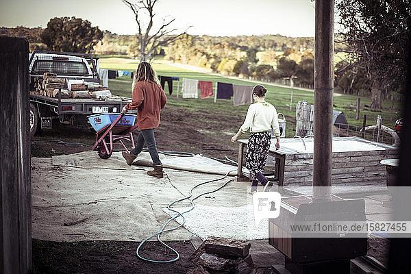 Junges Ehepaar auf dem Bauernhof sammelt in der Abenddämmerung Feuerholz von der Ladefläche eines Lastwagens